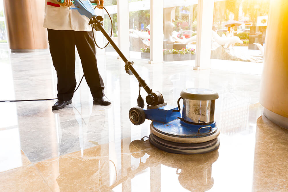 Cleaning man washing and polishing floor with machine in commercial building