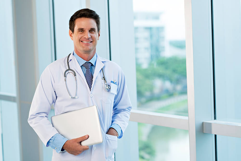 Smiling doctor standing with laptop and notebook