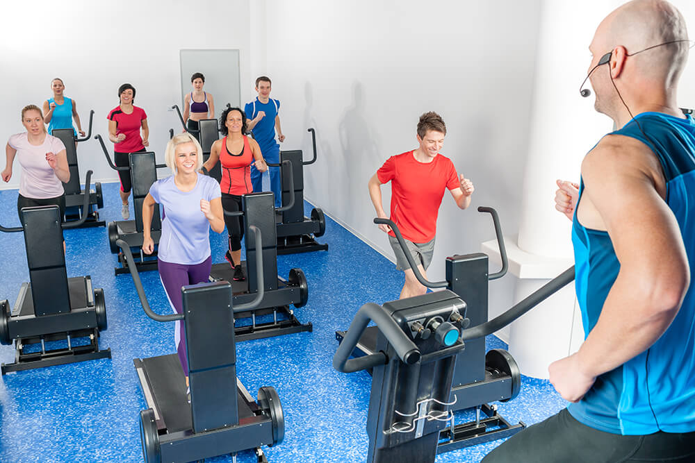 Group fitness class on fitness machine with personal trainer