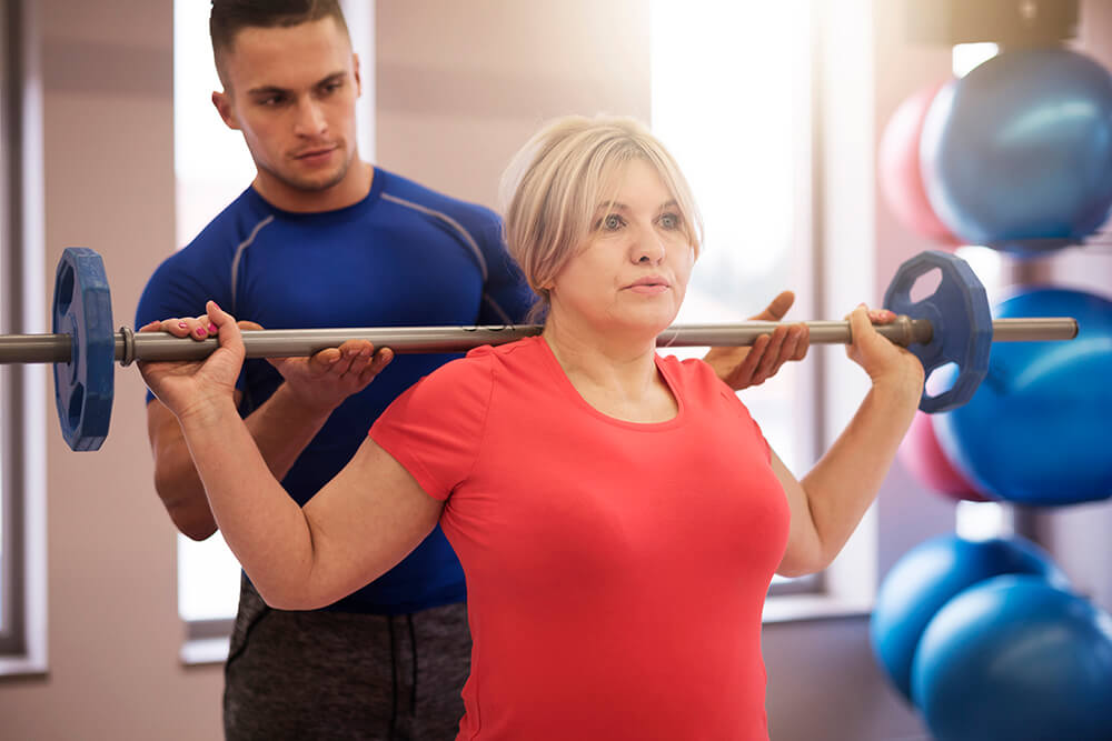 Man training and teaching woman how to work out in the gym