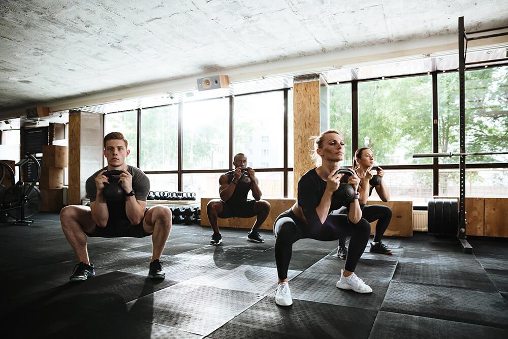 Fitness class doing kettlebell squats