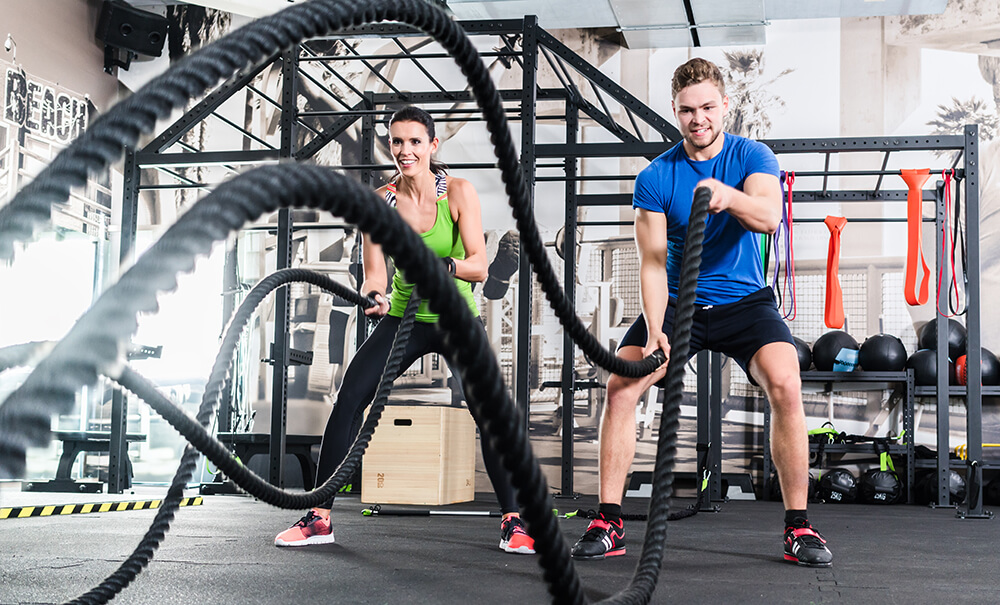 Man and woman working out together in the gym doing battle ropes