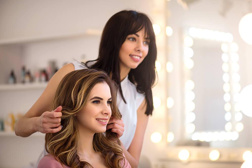 Woman getting a haircut by a hairstylist in hair salon