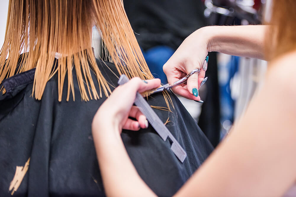 Woman getting a haircut by a hairstylist
