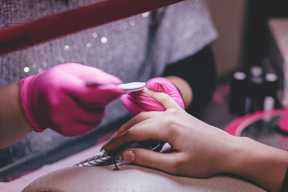 Woman getting a manicure done at a nail salon