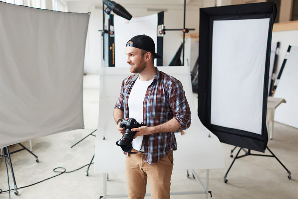 Photographer man with his camera in a photography studio