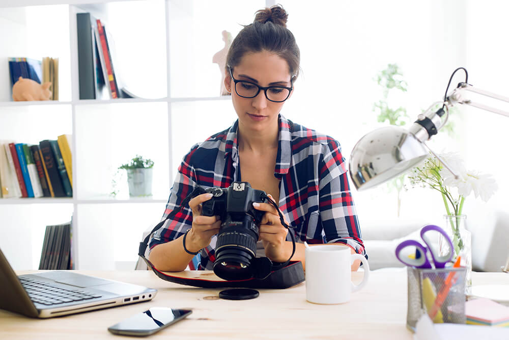 Woman photographer looking at her DSLR camera at her desk