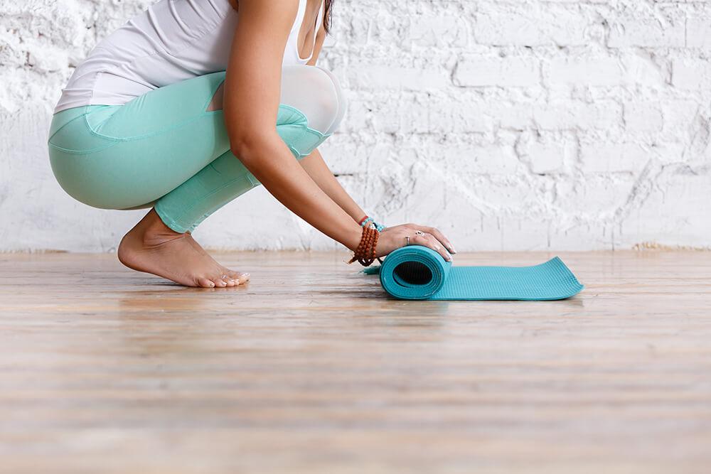 Yogi rolling up a yoga mat in yoga class